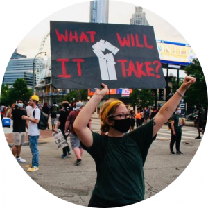 "protester with sign reading ""what will it take"""