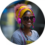 black woman smiling with pink hair wearing sunglasses and pink headphones