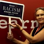"Debby holding a blue sign reading ""Make racism WRONG AGAIN!"""