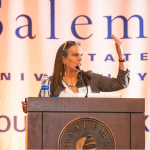 "Debby speaking at a podeum in front of sign reading ""Salen State University"""