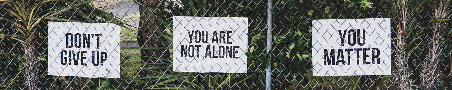 three signs behind fence: don't give up, you are not alone, you matter
