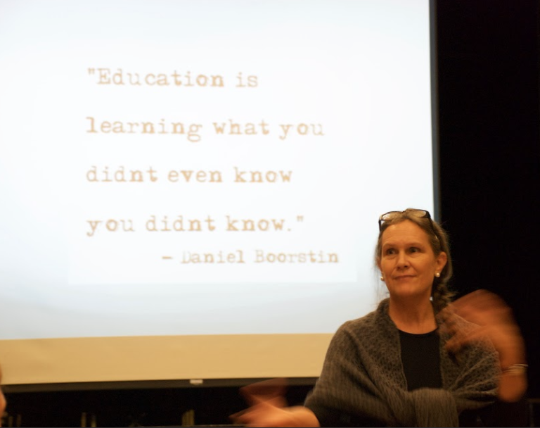 "Debby Irving standing in front of a slide reading ""Education is learning what you didn't even know you didn't know."" -Daniel Boorstin"