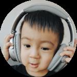 brown toddler adjusting closed-back headphones on head