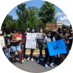 """black activists holding signs reading """"Love not hate"""", """"Why is my blackness such a thread?"""", """"BLM"""", """"Equality"""", """"Stop killing us"""""""