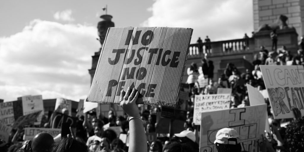 black and white photo of crowd of protesters holding signs No Justice No Peace in center